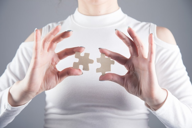 Jeune fille tient deux pièces de puzzle