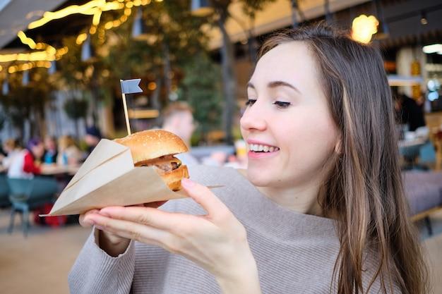 La jeune fille tient un hamburger dans ses mains et le regarde.