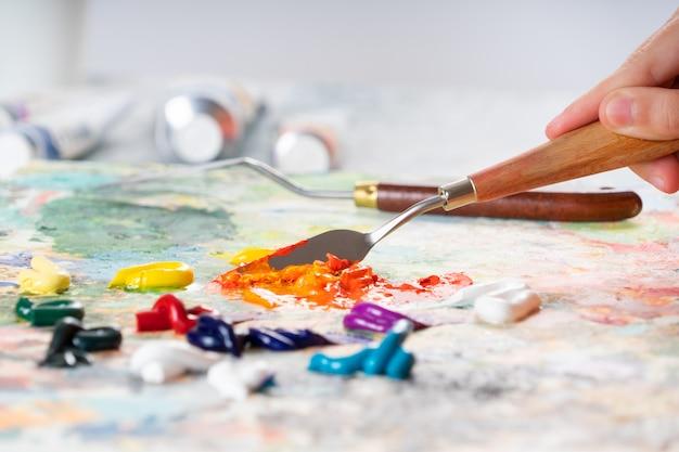 Une jeune fille tient à la main un couteau à palette pour dessiner et mélange des peintures huilées.