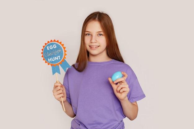 La jeune fille tient une pancarte chasse aux oeufs et oeuf de pâques
