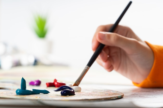 Une jeune fille tient un pinceau à la main et le trempe dans la peinture à l'huile. le processus de mélange des couleurs sur la palette.