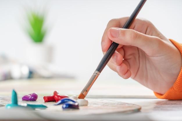 Une jeune fille tient un pinceau à la main et le trempe dans la peinture à l'huile.