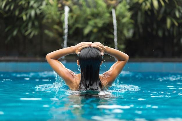 La jeune fille tient ses mains sur sa tête dans la piscine.