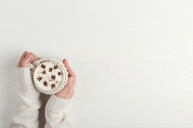 La jeune fille tient une tasse de boisson chaude de l'hiver avec de la crème fouettée