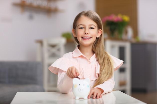 Jeune fille avec tirelire assis à table