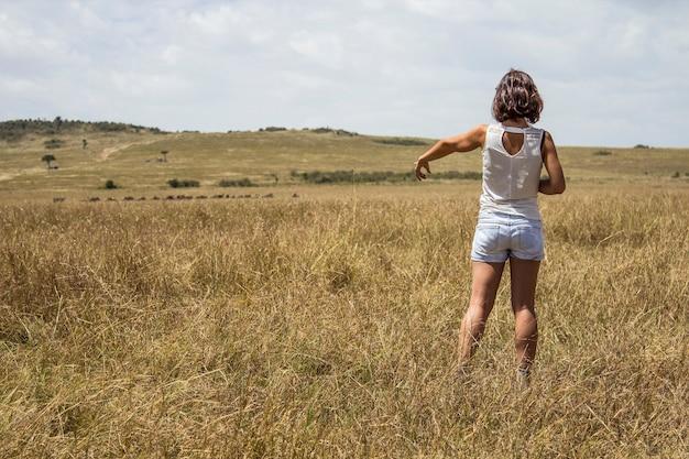 Une jeune fille touristique européenne profitant de l'intérieur du parc national du masai mara, des animaux en liberté dans la savane. kenya, afrique