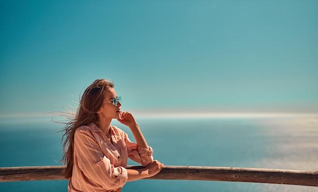 Jeune fille touristique mignonne à lunettes de soleil, vêtue d'un jean et d'une chemise se tient près d'une clôture en bois au sommet d'une falaise, sur fond de mer.