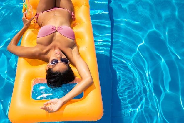 Jeune fille en train de bronzer sur un matelas pneumatique dans la piscine