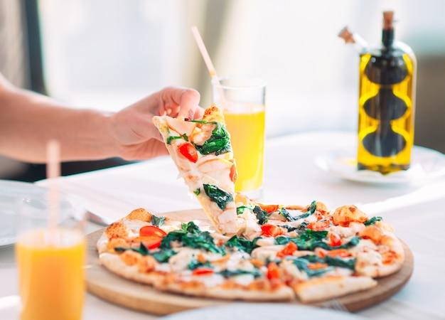 Jeune fille en train de manger une pizza au restaurant