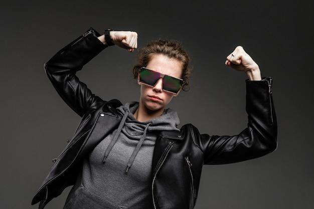 Une jeune fille avec des traits du visage rugueux dans une veste noire montre ses muscles isolés sur le mur noir