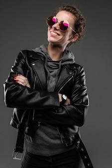 Une jeune fille avec des traits du visage rugueux dans une veste noire sourit isolé sur mur noir