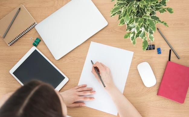 Jeune fille travaillant au bureau à domicile à la table