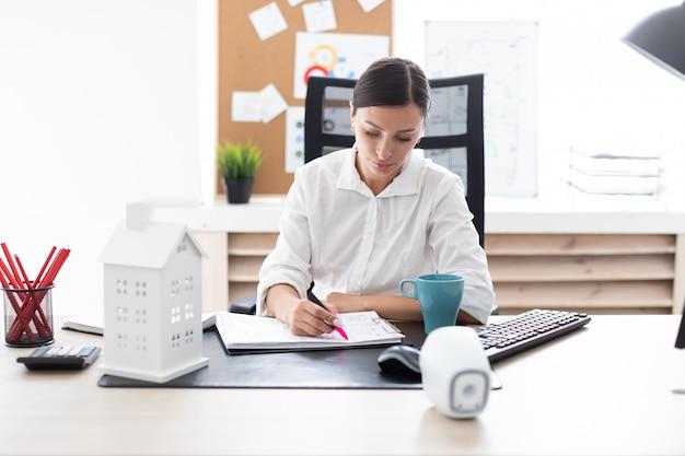 Une jeune fille travaillant dans le bureau à l'ordinateur.