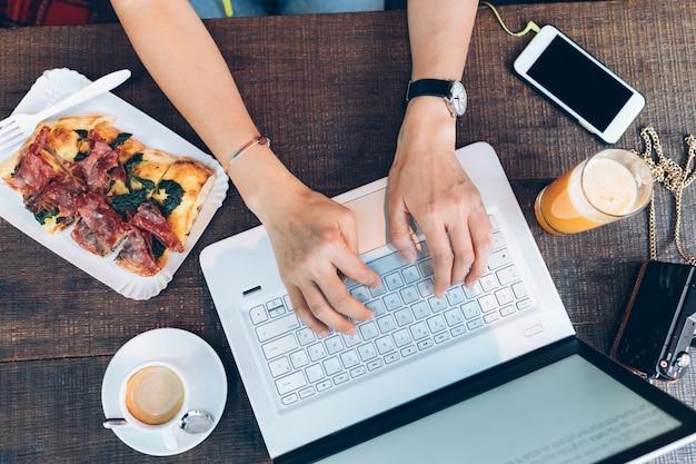 Jeune fille travaillant avec un ordinateur portable en mangeant une pizza