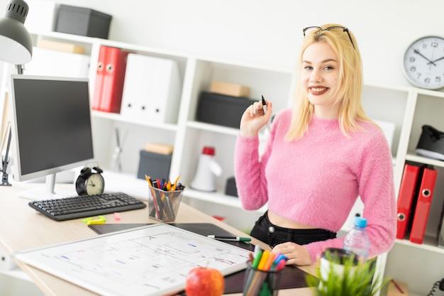 Une jeune fille travaille au bureau avec un marqueur et un tableau magnétique.
