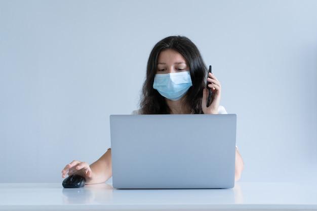La jeune fille travaille à domicile pendant la quarantaine. pandémie de corona virus. une fille dans un masque chirurgical travaille sur un ordinateur portable. travail éloigné