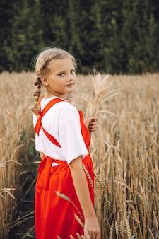 Une jeune fille avec des tresses et une robe rouge se promène dans un champ de blé
