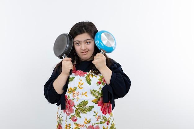 Jeune fille trisomique en tablier couvrant ses oreilles avec des poêles à frire.