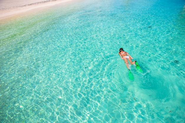 Jeune fille avec tuba dans l'eau tropicale en vacances