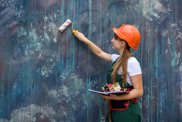 Jeune fille en uniforme peint un mur.