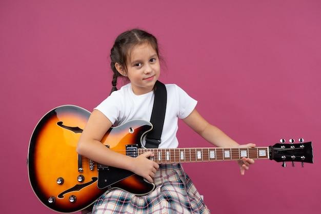 Une jeune fille en uniforme scolaire joue de la guitare électrique