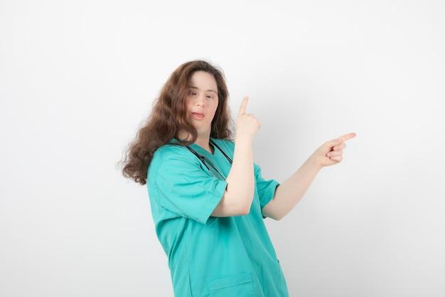 Jeune fille en uniforme vert debout et pointant vers l'extérieur.