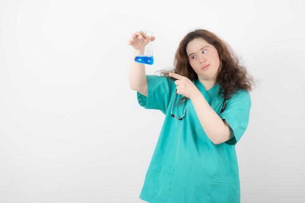 Jeune fille en uniforme vert pointant vers un bocal en verre avec du liquide bleu.