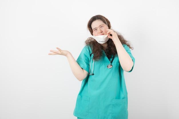 Jeune fille en uniforme vert portant un masque médical.