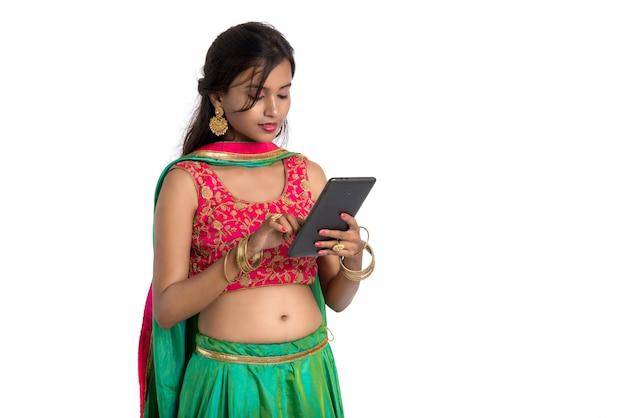 Jeune fille utilisant un téléphone mobile ou un smartphone sur blanc