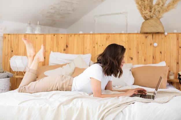 Une jeune fille utilise un ordinateur portable au lit pour travailler à distance depuis la maison