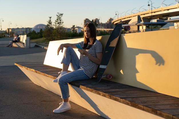 Jeune fille utilise un smartphone à l'extérieur dans un parc urbain en discutant avec des amis dans un messager de téléphone portable