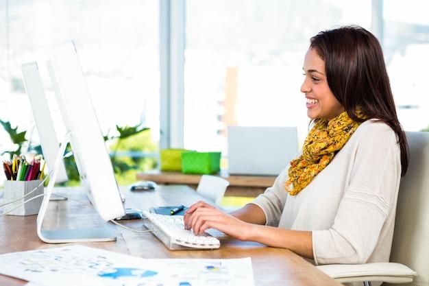 Jeune fille utilise son ordinateur dans un bureau