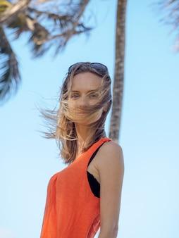 Jeune fille en vacances dans un gilet orange et des lunettes de soleil sur une île tropicale. soufflant une forte brise de l'océan