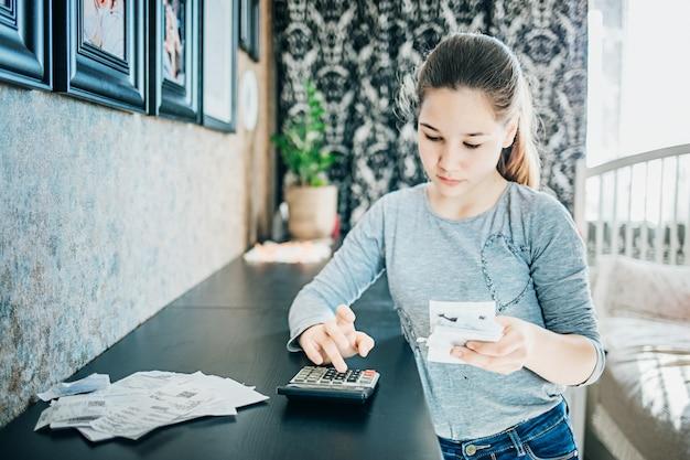 Jeune fille vérifie les factures dans sa chambre. il y a des pièces devant elle. mise au point sélective