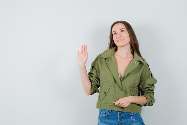 Jeune fille en veste, short en agitant la main pour dire au revoir et à la joyeuse vue de face.