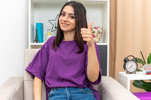 Jeune fille en vêtements décontractés à la recherche de sourire gaiement heureux et positif montrant les pouces vers le haut assis sur une chaise dans un salon lumineux