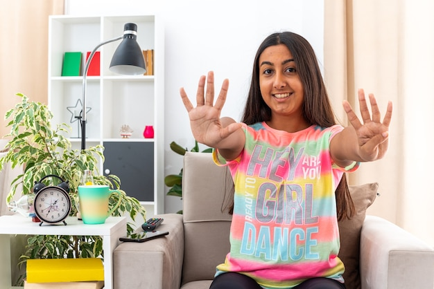 Jeune fille en vêtements décontractés à la recherche de sourire gaiement montrant le numéro neuf avec les doigts assis sur la chaise dans un salon lumineux