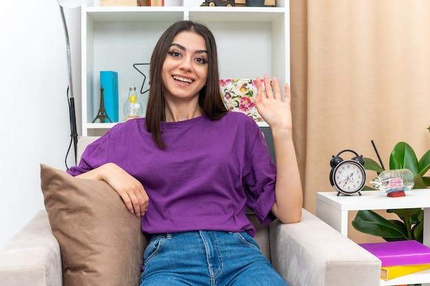 Jeune fille en vêtements décontractés à la recherche de sourire heureux et positif agitant joyeusement avec la main souriant joyeusement assis sur une chaise dans un salon lumineux