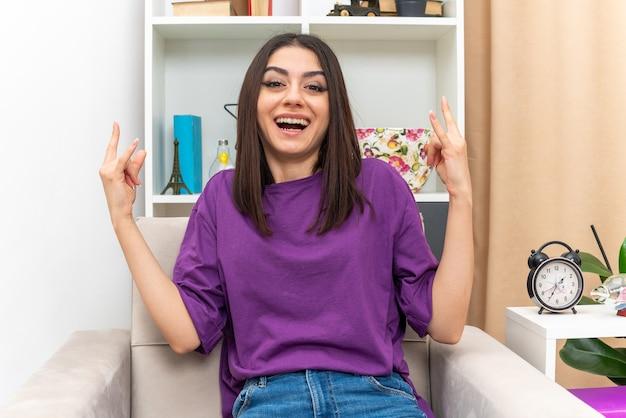 Jeune fille en vêtements décontractés à la recherche de symbole de rock heureux et excité assis sur une chaise dans un salon lumineux