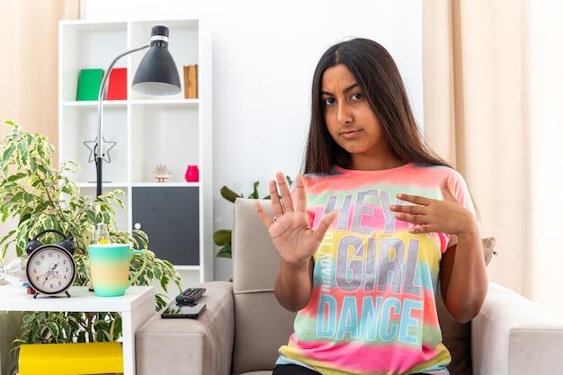 Jeune fille en vêtements décontractés regardant la caméra avec un visage fronçant grave faisant le geste d'arrêt avec la main assise sur la chaise dans la salle de séjour lumineuse