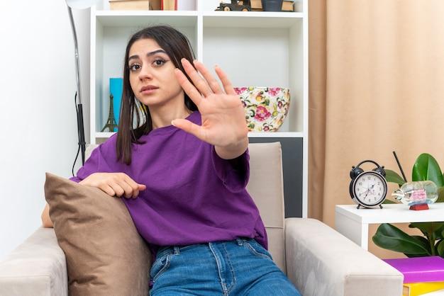 Jeune fille en vêtements décontractés regardant avec un visage sérieux faisant un geste d'arrêt avec la main assise sur une chaise dans un salon lumineux