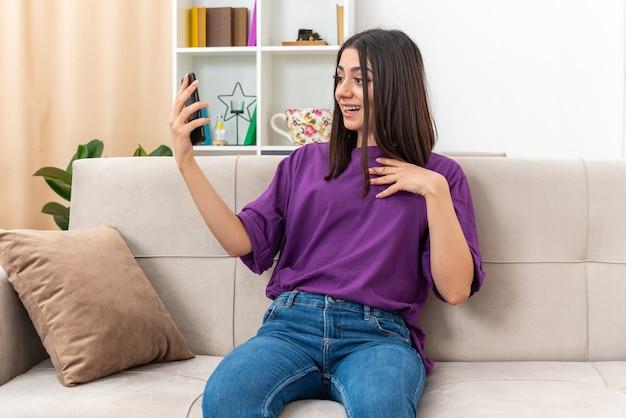 Jeune fille en vêtements décontractés tenant un smartphone ayant un appel vidéo heureux et positif souriant confiant assis sur un canapé dans un salon lumineux