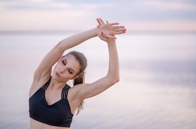 Jeune fille en vêtements de fitness au bord de la mer effectue des exercices