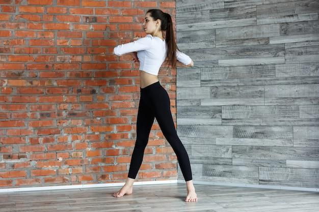 Jeune fille en vêtements noir et blanc se réchauffe avant un entraînement dans la salle de gym