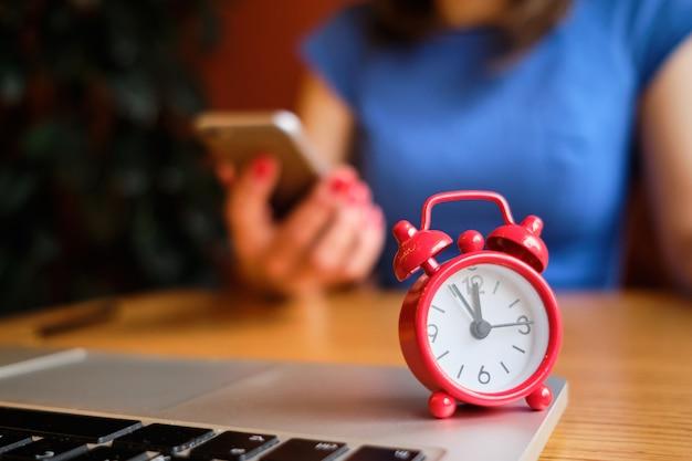 Une jeune fille vêtue d'une robe bleue travaille dans un smartphone au premier plan une horloge rouge. date limite de concept.