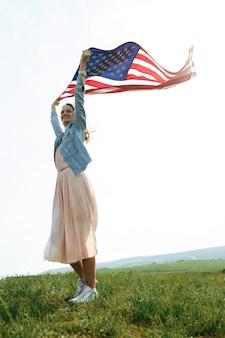 Une jeune fille vêtue d'une robe corail et d'une veste en jean tient le drapeau des états-unis dans ses mains. 4 juillet fête de l'indépendance.