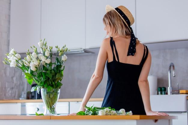 Jeune fille vêtue d'une robe noire près de bouquet de roses blanches dans un vase