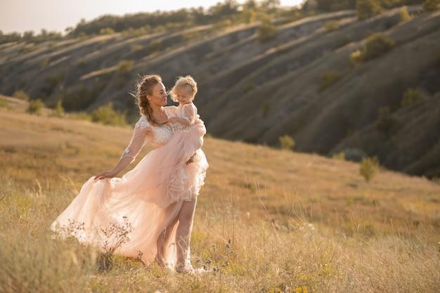Jeune fille vêtue d'une robe rose aérée tient une petite fille dans ses bras