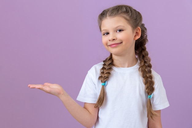Une jeune fille vêtue d'un t-shirt blanc et de nattes pointe vers le côté.