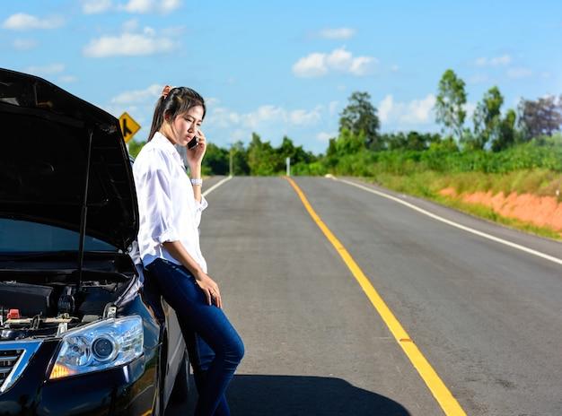 Jeune fille avec une voiture en panne avec capot ouvert: appel à l'aide